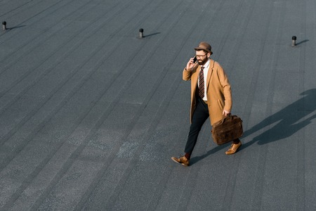 confident businessman in hat and coat walking on roof and talking on smartphone Zdjęcie Seryjne - 116293132