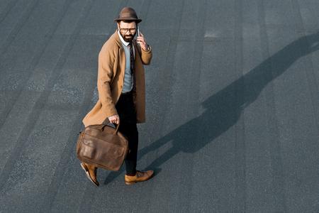 confident businessman walking on roof and talking on smartphone Zdjęcie Seryjne - 116293142