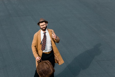 bearded businessman holding smartphone and looking at camera