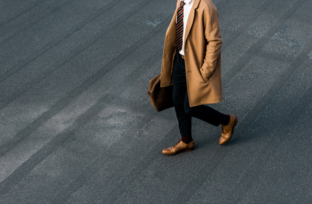 partial view of businessman in coat with bag walking on grey roof
