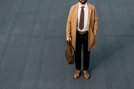 cropped view of bearded businessman standing with leather brown bag