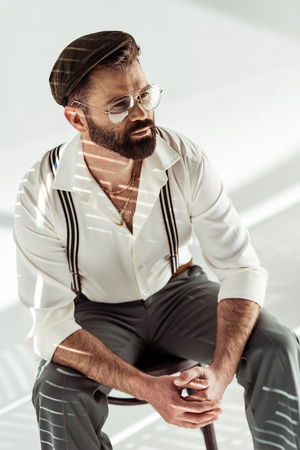 handsome bearded man with clenched hands sitting on chair on white background