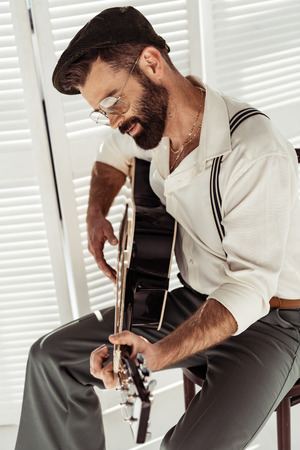 handsome bearded man sitting on chair and playing acoustic guitar near folding screen in room