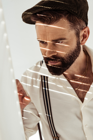 handsome bearded man looking through room divider