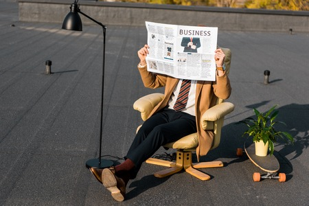 businessman with obscure face sitting in armchair and holding business newspaper