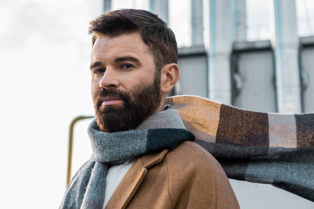 close up of bearded businessman in scarf and coat
