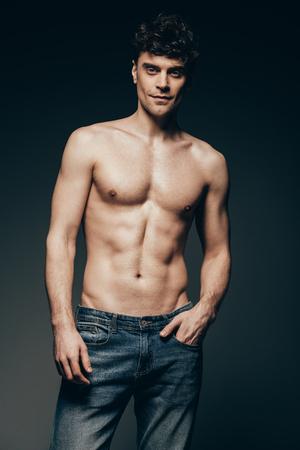 Gut aussehender Mann mit nacktem Oberkörper in Jeans posiert isoliert auf dunkelgrau Standard-Bild