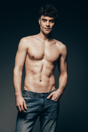 handsome shirtless man in jeans posing isolated on dark grey