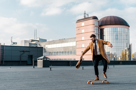 bearded businessman riding on penny board with bag in hand