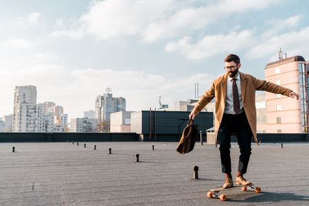 Handsome businessman riding on penny board on roof
