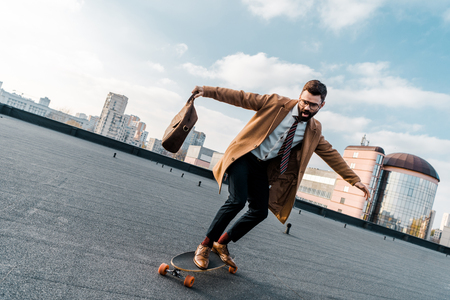 excited businessman riding on penny board with bag in hand Zdjęcie Seryjne