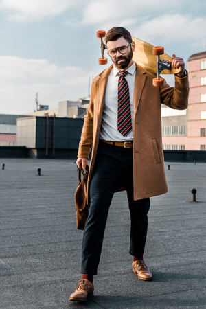 bearded businessman standing in formalwear and coat with penny board and bag in hands