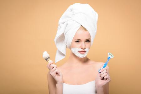 junge Frau mit Handtuch auf dem Kopf und Rasierschaum im Gesicht mit Rasiermesser und Rasierpinsel isoliert auf Beige