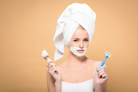 young woman with towel on head and shaving cream on face holding razor and shaving brush isolated on beige 免版税图像