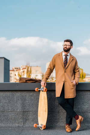 handsome businessman holding penny board  and standing with hand in pocket
