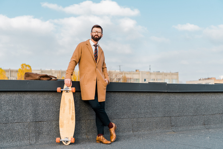 bearded businessman in glasses standing with penny board on roof