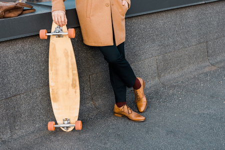 cropped view of businessman in coat holding penny board Stock Photo