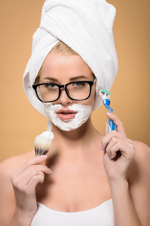 young woman with towel on head holding razor and shaving brush isolated on beige Stock Photo