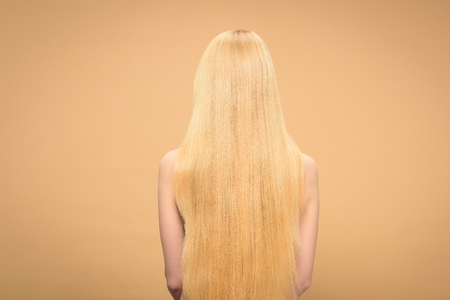 Back view of long-haired blonde woman standing on beige background Stock Photo