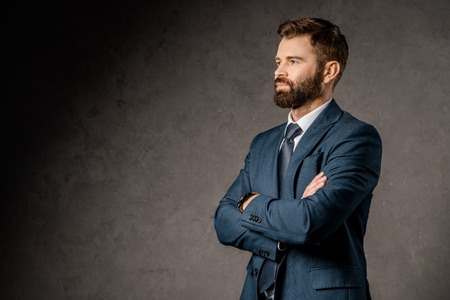 successful bearded businessman standing with crossed arms Stock Photo