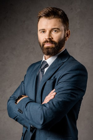 confident bearded businessman standing with crossed arms Stock Photo