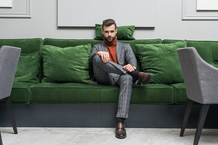 man in formal wear with legs crossed sitting on green sofa and looking at camera