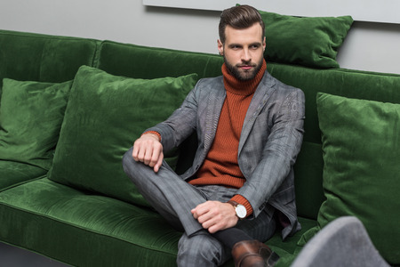 man in formal wear with legs crossed sitting on green sofa