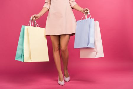 cropped view of woman in dress holding shopping bags, isolated on pink