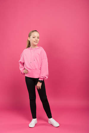 pretty athletic kid posing in sportswear, on pink