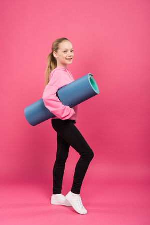 blonde youngster in sportswear holding fitness mat, isolated on pink Foto de archivo