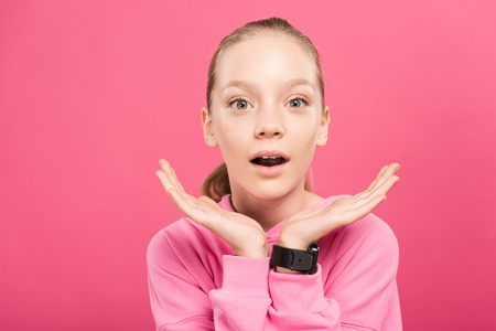 surprised blonde kid looking at camera, isolated on pink Stockfoto