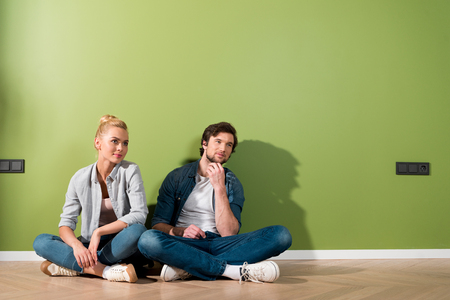 thoughtful couple sitting on floor by green wall