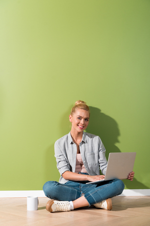 beautiful girl with laptop sitting on floor by green wall and looking at camera Stock Photo