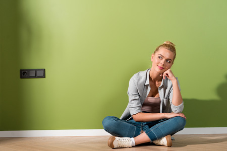 thoughtful girl smiling and sitting on floor by green wall Stock Photo