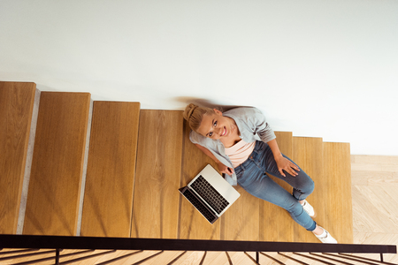 overhead view of attractive girl sitting with laptop on stairs and looking at camera