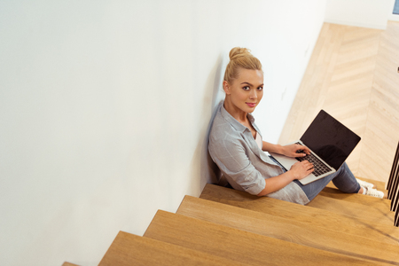 beautiful girl sitting on stairs, typing on laptop keyboard and looking at camera