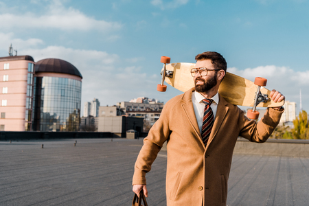 cheerful businessman holding penny board and smiling on roof