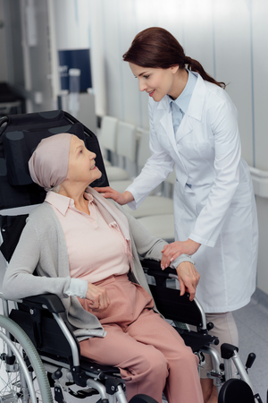 smiling female doctor near senior woman in kerchief with cancer sitting in wheelchair in hospital 스톡 콘텐츠