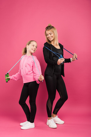 sporty mother and adorable daughter holding jump ropes, isolated on pink