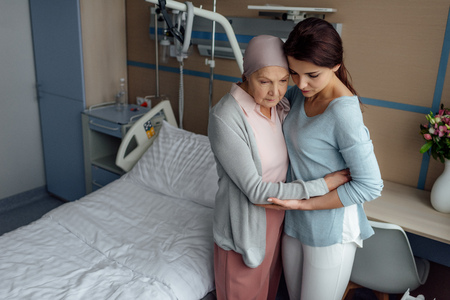 upset daughter embracing sick senior mother with cancer in hospital