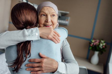 smiling senior woman in kerchief hugging daughter in hospital Фото со стока