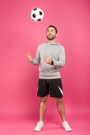 handsome sportsman throwing up soccer ball isolated on pink