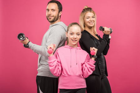 sportive family training with dumbbells, isolated on pink Zdjęcie Seryjne