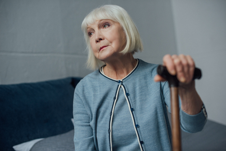 lonely senior woman sitting on bed with walking stick at home Stock Photo