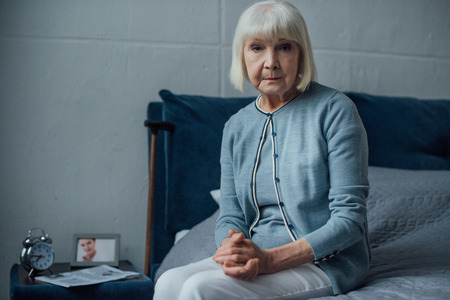 senior woman looking at camera and sitting on bed with folded hands at home