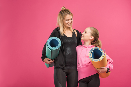 happy mother and sporty daughter holding fitness mats, isolated on pink