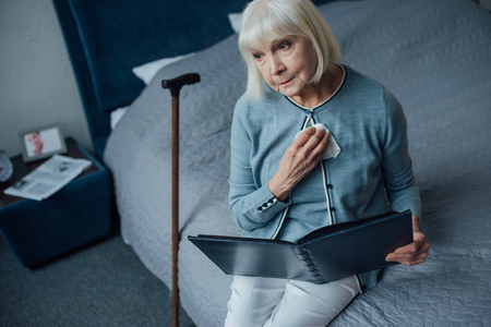 sad senior woman sitting on bed and holding photo album with handkerchief at home