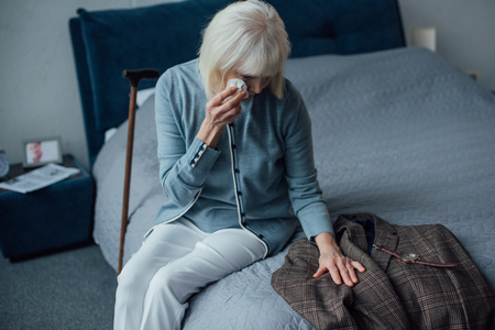 crying senior woman sitting on bed, wiping tears and looking at jacket at home
