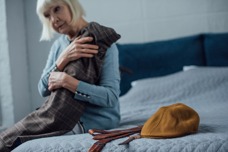 sad senior woman sitting on bed and holding jacket at home Stock Photo