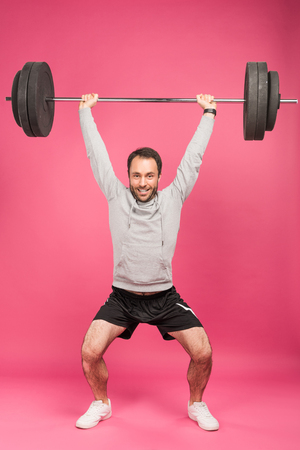 strong sportsman training with barbell, isolated on pink